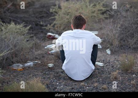 Teenage boy boire de l'alcool à l'extérieur, assise dans la saleté avec des bouteilles vides. Photo Stock