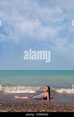 Une jeune fille couchée dans un lac dans les vagues Photo Stock