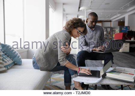 Les designers d'intérieur à l'aide d'ordinateurs portatifs dans office Photo Stock