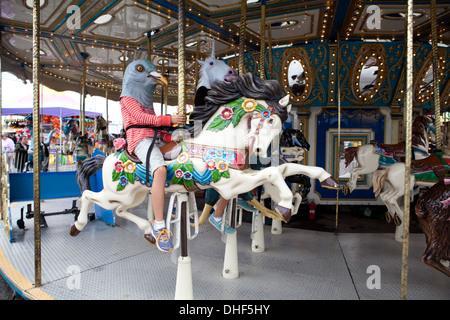 Jeune fille portant un masque de pigeon à cheval sur le carrousel. Photo Stock