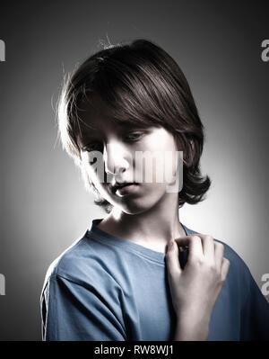 Portrait d'un garçon avec les cheveux bruns en haut bleu. Photo Stock