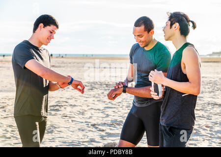 Coureurs homme contrôle smart watch trackers fitness sur sunny beach Photo Stock