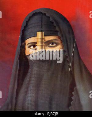 Femme égyptienne dans un voile intégral (burko a) fait de crêpe noir avec un cylindre doré en l'éloignant de son nez et de la bouche, de l'Égypte. Photo Stock