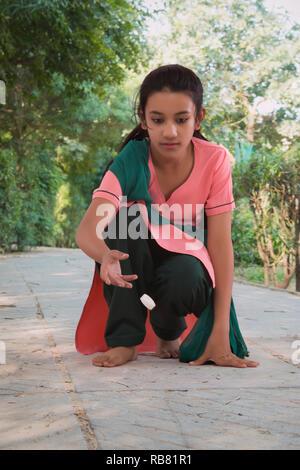Jouer jeu fille rurale hopping in park Photo Stock