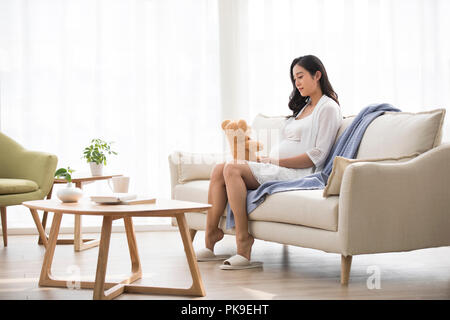 Cheerful pregnant woman Playing with teddy bear Photo Stock