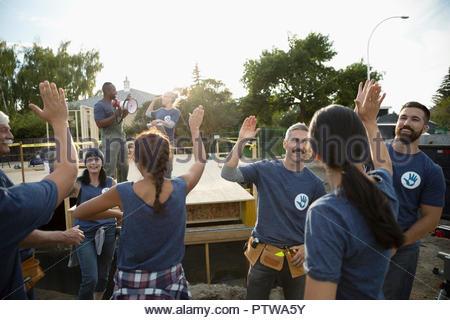 Haut de volontaires enthousiastes et on subit donc célébrer, aide à accroître la chambre Photo Stock