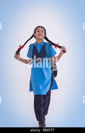 Portrait de jeune fille en uniforme scolaire rural livre sac et portefeuille Photo Stock