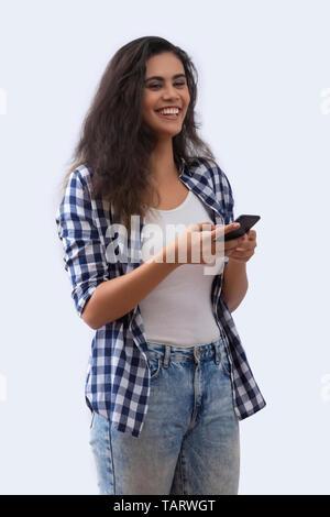 Femme en jeans et chemise en utilisant un téléphone mobile Photo Stock