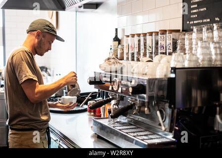 Homme barbu portant chapeau de base-ball debout à la machine à expresso d'un restaurant. Photo Stock