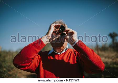 Un homme à l'aide de jumelles en pleine nature sur une journée ensoleillée Photo Stock