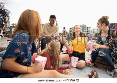 Les adolescents traînant, eating popcorn in urban park Photo Stock