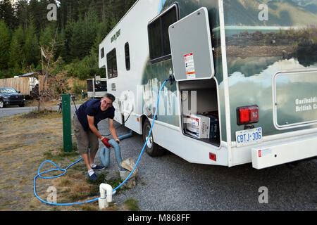 Locations de RV Canadian Rockies, Canada homme se vide réservoir de drainage en vacances parution modèle Photo Stock