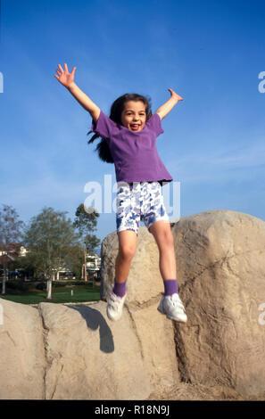 Jeune fille sautant d'un mur de pierre sur l'aire de jeux. M. © Myrleen Pearson ...Ferguson Cate Photo Stock