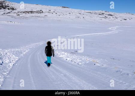 Une personne qui marche sur une route enneigée Photo Stock