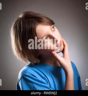 Portrait d'un garçon avec les cheveux bruns de penser. Photo Stock