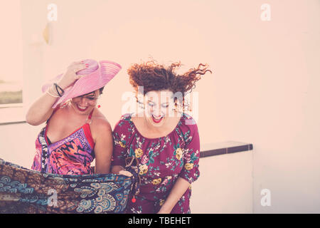 Crazy et cheerful couple de young Caucasian women friends beaucoup rire - les gens s'amuser en plein air partie de couleur claire backgroun lumineux - festival Photo Stock