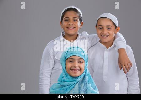 Deux frères debout avec leur sœur en face Photo Stock