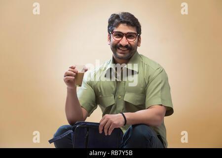 Smiling man wearing eyeglasses tenant une petite pochette dans une main et un verre de thé dans l'autre. Photo Stock