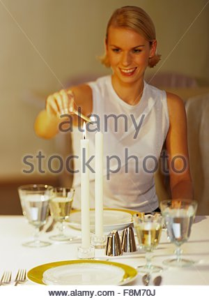 Une jeune femme allumant une bougie sur la table Photo Stock