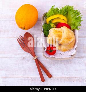Petit-déjeuner de l'alimentation propre croissant et salade sur table en bois. Photo Stock