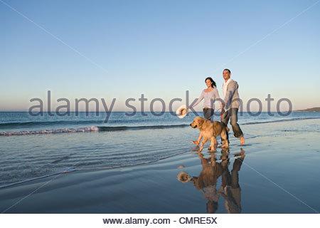 Couple en train de marcher leur chien par la mer Photo Stock