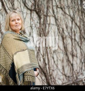 Senior woman in permanent châle contre mur recouvert de lierre sans feuilles Photo Stock
