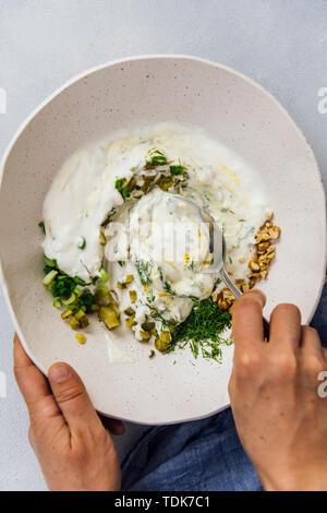 Woman mixing les ingrédients d'une recette de salade de poulet low carb dans un bol en céramique Photo Stock