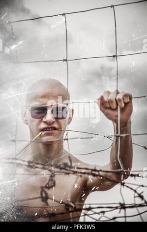 Jeune homme derrière la barrière dans la nature Photo Stock