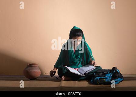 La fille rurale en costume traditionnel assis sur le plancher et l'étude Photo Stock