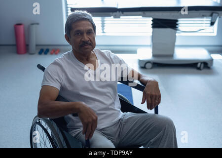 Vue avant du mixed race male patient looking at camera while sitting in wheelchair in hospital Photo Stock