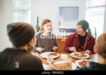 Petit déjeuner aux crêpes en famille à table Photo Stock