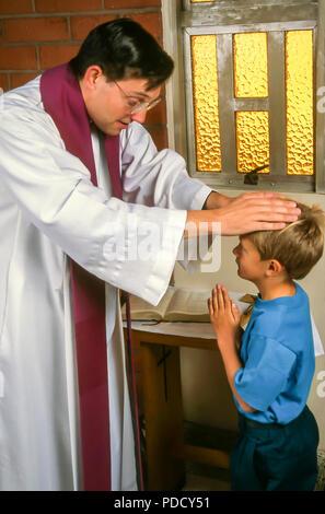 Prêtre bénit petit garçon à la réconciliation M. © Myrleen Pearson ...Ferguson Cate Photo Stock