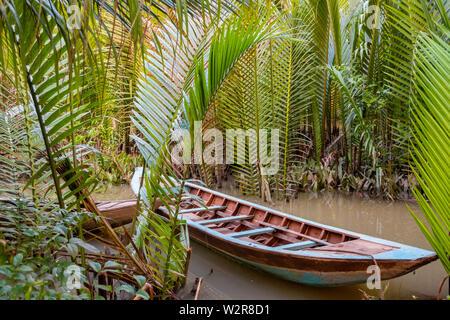 Bateau traditionnel amarré entre palmiers dans le Delta du Mékong, au Vietnam. Photo Stock