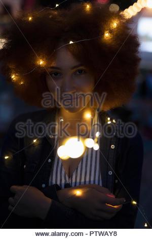 Portrait jeune femme confiante enveloppé dans string lights Photo Stock