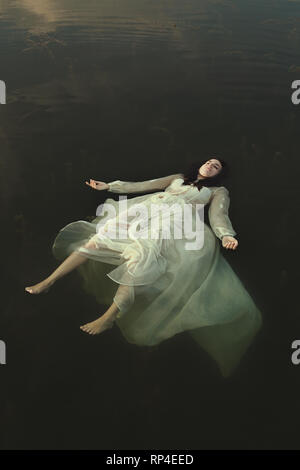 Femme flottant dans les eaux du lac vert Photo Stock