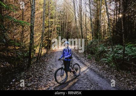 Portrait homme confiant à VTT dans les bois d'automne, Squamish, BC, Canada Photo Stock