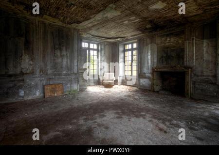Vue intérieure d'une chambre avec une chaise dans un coin de la fenêtre dans un château abandonné en France. Photo Stock