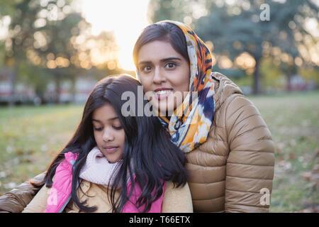 Portrait smiling mother en hijab sitting in autumn park avec fille Photo Stock