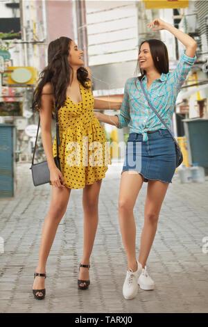 Deux femmes marchant sur l'écoute de la musique de rue Photo Stock
