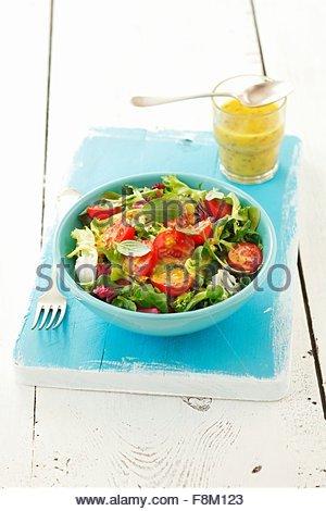 Les feuilles de salade avec les tomates cerise et vinaigrette à la moutarde et au miel Photo Stock
