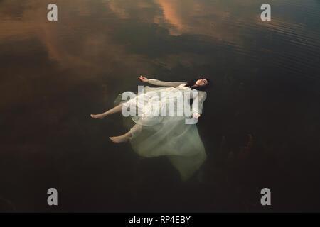 Innocent girl sleeping in dark waters Photo Stock