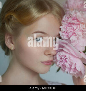 Close up of Caucasian teenage girl holding Flowers à face Photo Stock