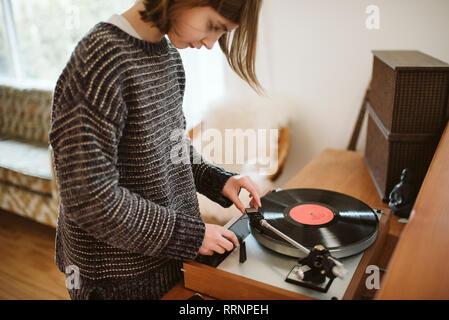 Girl playing vinyl record dans la salle de séjour Photo Stock