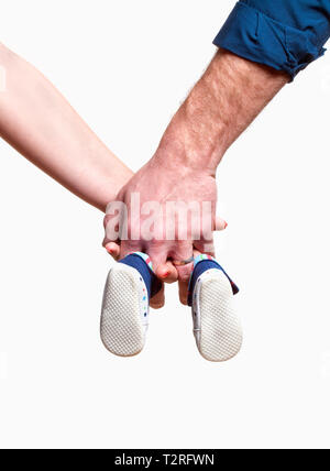 Expecting Couple avec Hands Holding Baby Shoes. Photo Stock