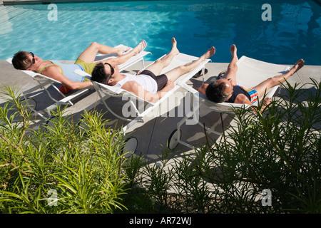 Les hommes de vous détendre dans les chaises de parterre à côté piscine Photo Stock