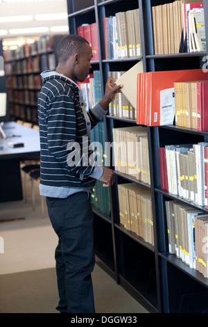 Jeune étudiant noir atteint pour un livre de bibliothèque de l'école. Photo Stock