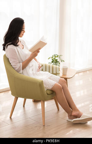 Cheerful pregnant woman reading book at home Photo Stock
