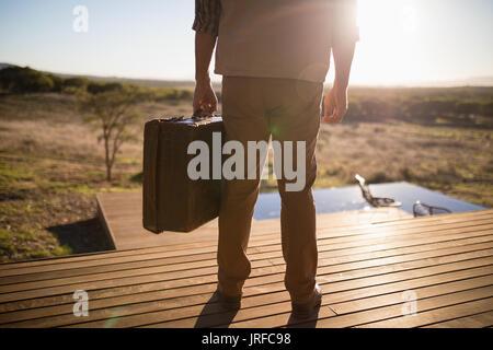 La section basse de l'homme avec valise debout sur planche en bois Photo Stock