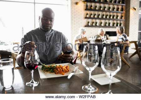 Man with smart phone manger dans restaurant Photo Stock