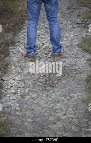 Les jambes de l'homme debout sur la terre craquelée Photo Stock